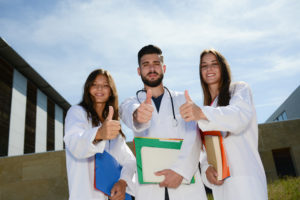 Group of young happy medical students boys and girls together on hospital university campus